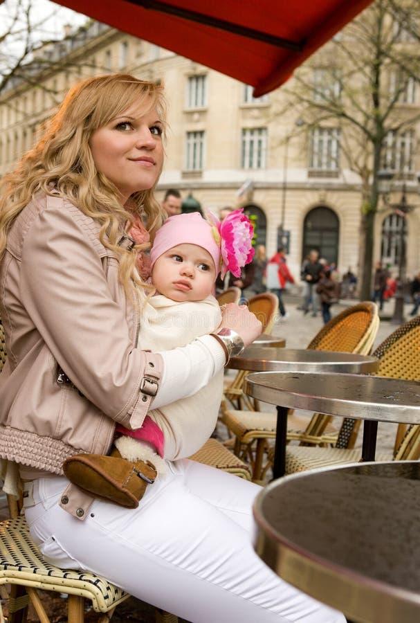 Sirva de madre y su hija en café parisiense de la calle fotos de archivo