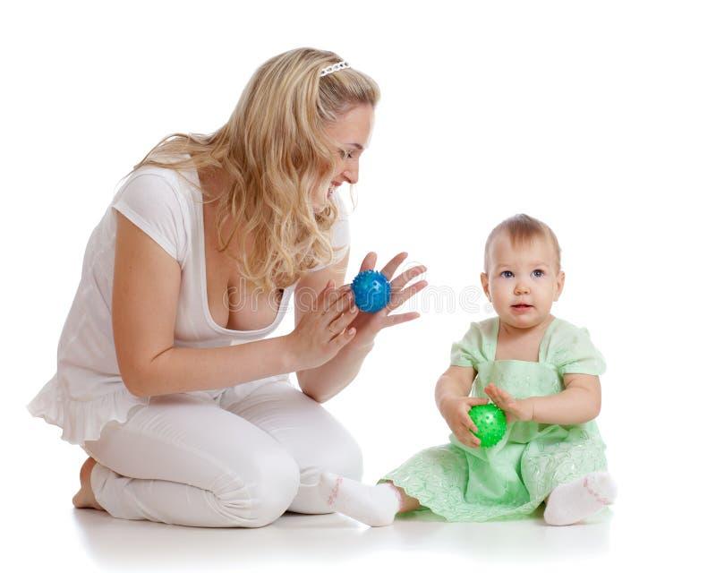 Sirva de madre y su masaje del niño con los dispositivos de goma foto de archivo libre de regalías