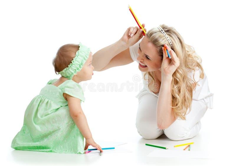 Sirva de madre y sus juegos de diversión del niño con los lápices del color foto de archivo libre de regalías