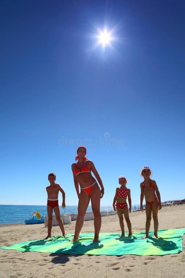 Sirva de madre y sus niños en la playa imágenes de archivo libres de regalías
