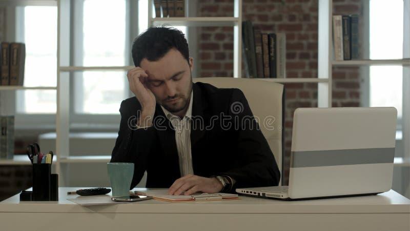 Sirva dormir en un escritorio, despierte y comience a hablar el teléfono imagenes de archivo