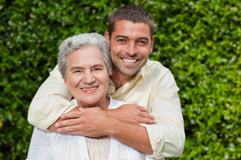 Sirva el abrazo de su madre en el jardín foto de archivo