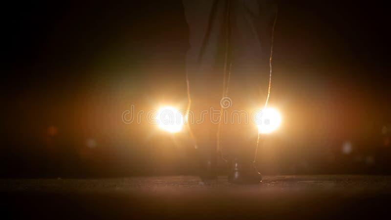 Sirva el acercamiento al coche con las linternas encendido, las negociaciones de la noche con los bandidos foto de archivo libre de regalías