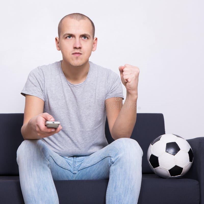Sirva el aficionado al fútbol que se sienta en el sofá con la bola y la TV de observación en casa imagenes de archivo