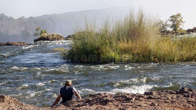 Sirva el ajuste en el lado del río Zambezi en Victoria Falls, Zambia imagen de archivo