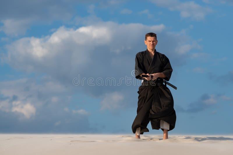 Sirva el arte marcial japonés practicante - iaido en el desierto fotos de archivo libres de regalías