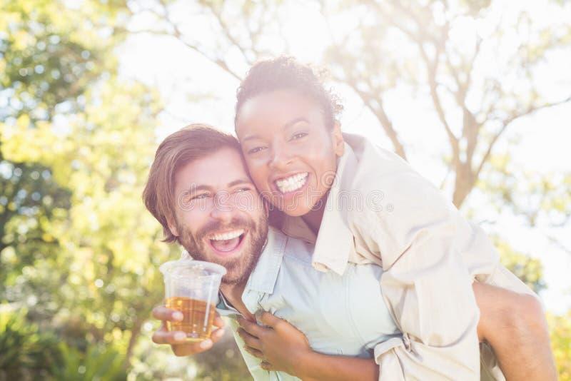 Sirva el donante a cuestas a la mujer mientras que comiendo el vidrio de cerveza foto de archivo