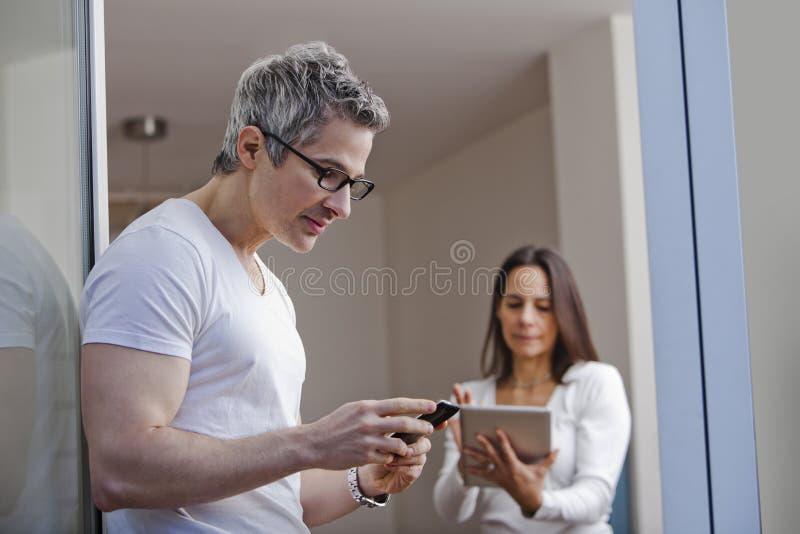 Sirva el envío de mensajes de texto con su esposa que usa una tableta digital imagen de archivo