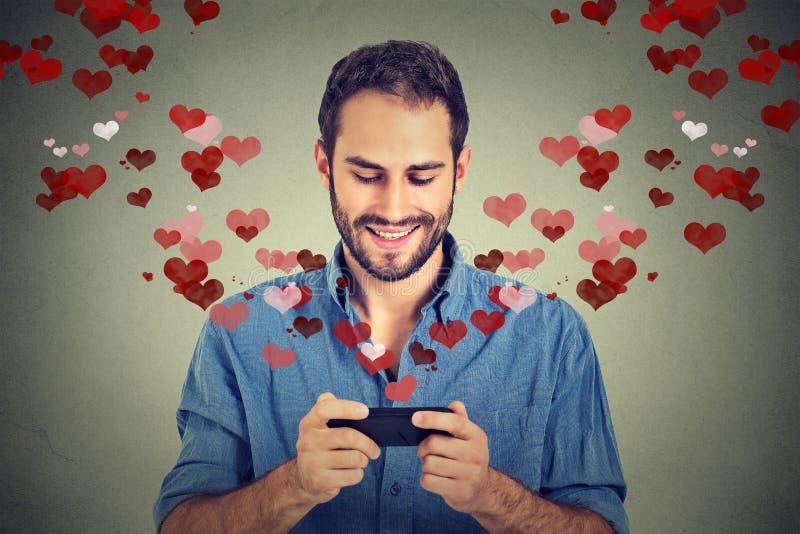 Sirva el envío del mensaje del SMS del amor en el teléfono móvil con los corazones que se van volando fotografía de archivo libre de regalías