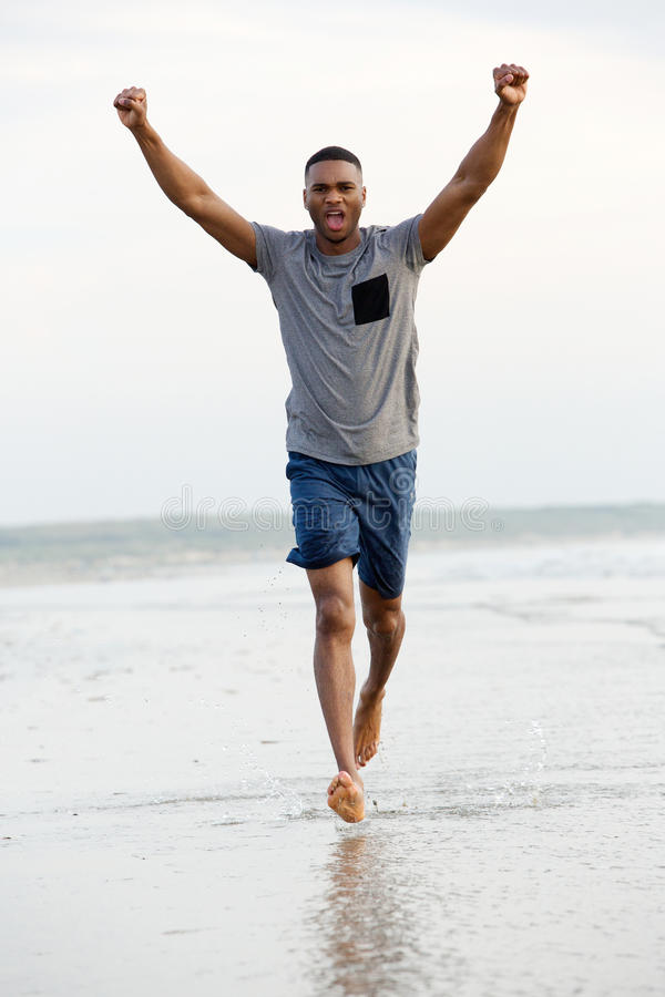 Sirva el funcionamiento descalzo en la playa con los brazos aumentados en la victoria imagen de archivo