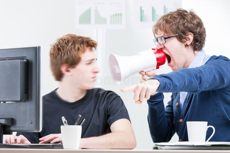Sirva el grito con un megáfono a su colega foto de archivo
