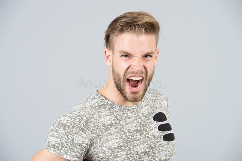 Sirva el grito enojado en camiseta en fondo gris imagen de archivo