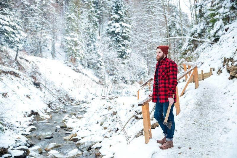 Sirva el hacha cercana derecha del río y de la tenencia de la montaña en invierno fotografía de archivo