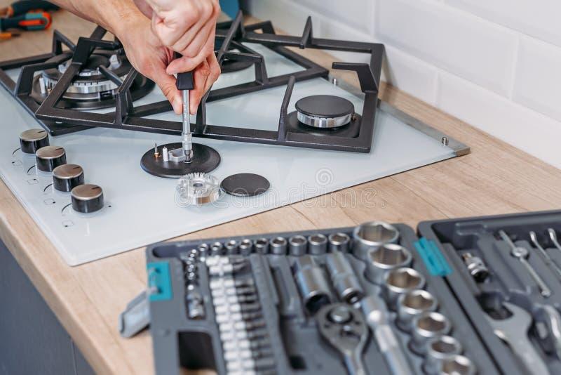 Sirva el hotplate de las reparaciones de la mano del ` s del panel de gas con destornillador foto de archivo libre de regalías