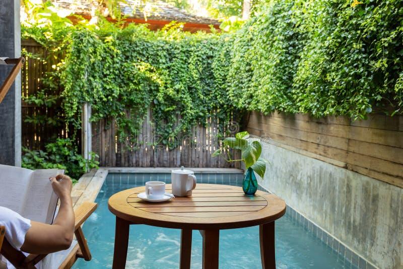 Sirva el libro de lectura por la piscina con la taza de café con la planta en fondo imagen de archivo