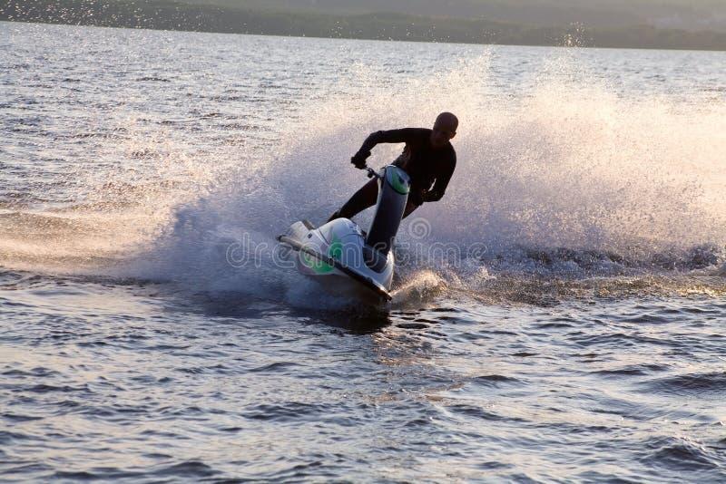 Sirva el montar a caballo en los esquís del jet en el mar foto de archivo