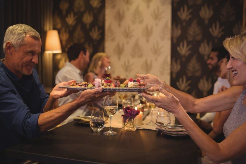 Sirva el paso de una placa de la comida a la mujer en la tabla imagenes de archivo