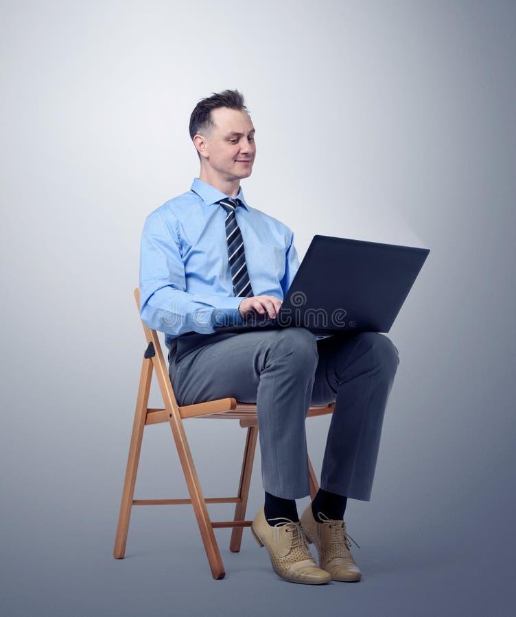 Sirva el programador con un ordenador portátil que se sienta en una silla en fondo oscuro foto de archivo