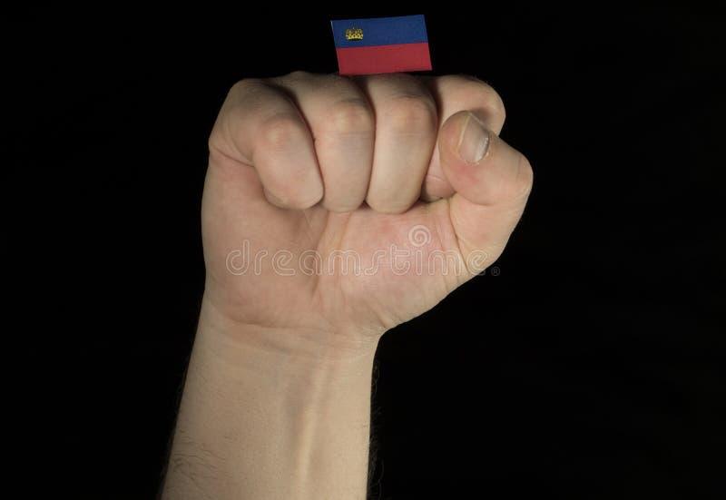 Sirva el puño de la mano con la bandera de Liechtenstein aislada en fondo negro imagenes de archivo