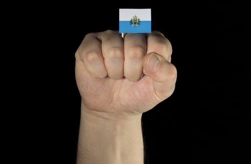 Sirva el puño de la mano con la bandera de San Marino aislada en negro imagen de archivo