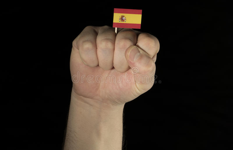 Sirva el puño de la mano con la bandera española aislada en negro fotografía de archivo