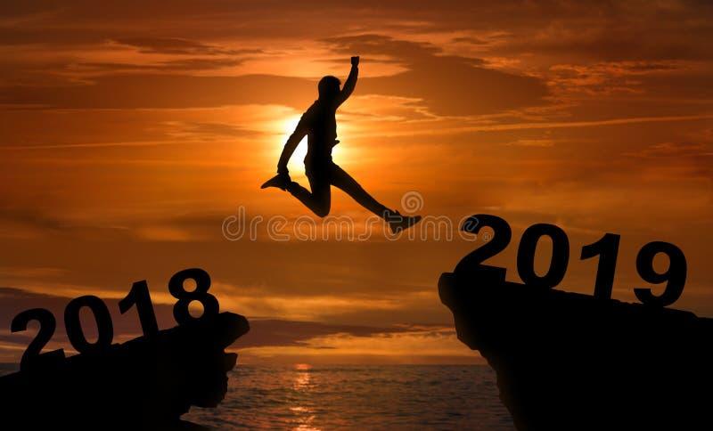 Sirva el salto entre 2018 y 2019 años en la puesta del sol imagen de archivo libre de regalías