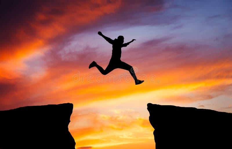 Sirva el salto a través del hueco a partir de una roca a aferrarse en la otra imagen de archivo