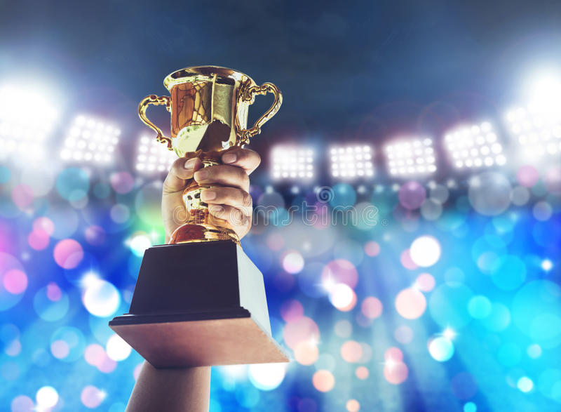 Sirva el soporte una taza del trofeo del oro, concepto del triunfo foto de archivo libre de regalías