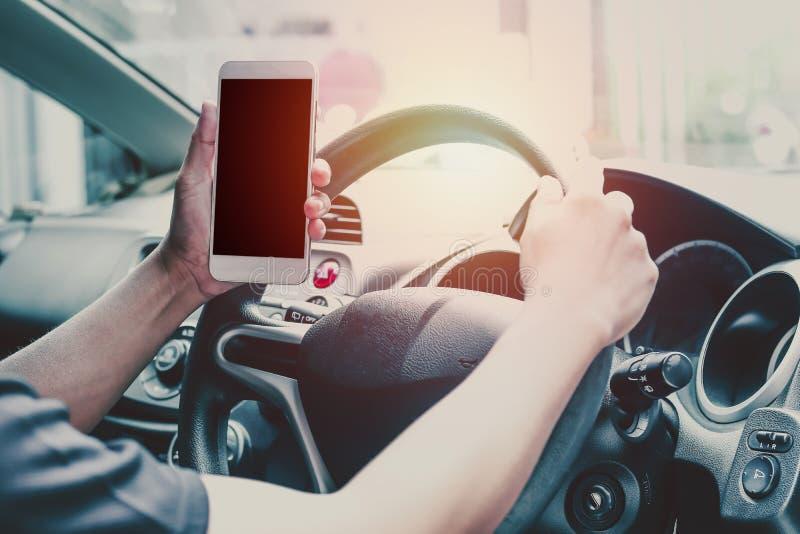 Sirva el teléfono del uso y la mirada en la pantalla vacía del móvil, concepto como mirada de la manera de calle debido al atasco foto de archivo libre de regalías