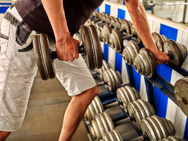 Sirva el trabajo de sus brazos con pesas de gimnasia en el gimnasio fotos de archivo libres de regalías
