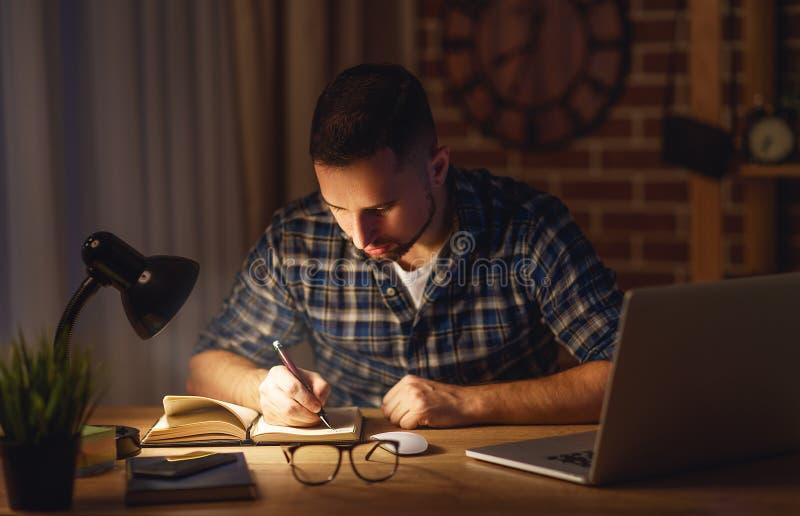 Sirva el trabajo en el ordenador en casa en la noche en oscuridad imágenes de archivo libres de regalías