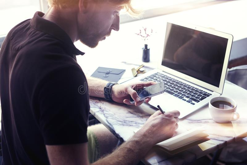 Sirva el trabajo en la oficina soleada en el ordenador portátil mientras que se sienta en el café que come café Concepto de hombr foto de archivo libre de regalías