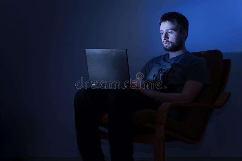 Sirva el trabajo en un ordenador portátil en un cuarto oscuro en la noche imagenes de archivo
