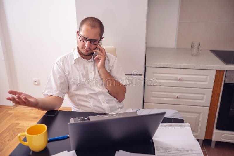 Sirva el trabajo y hablar en su teléfono en casa foto de archivo libre de regalías