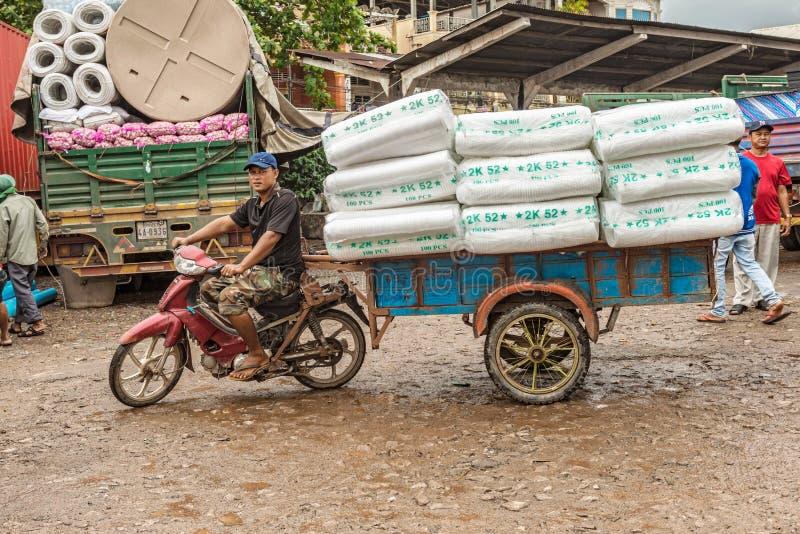 Sirva el transporte de mercancías usando su moto en Sihanoukville leva fotos de archivo libres de regalías