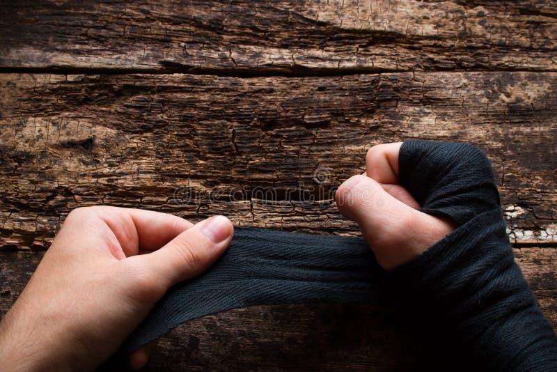 Sirva el vendaje su puño antes del boxeo en la tabla imagen de archivo libre de regalías