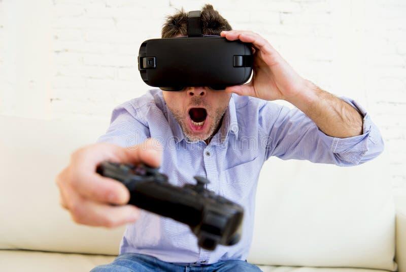Sirva en casa el sofá del sofá de la sala de estar emocionado usando juego de las gafas 3d fotos de archivo