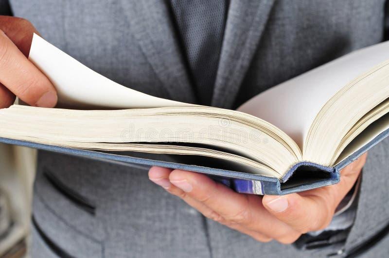 Sirva en el traje que lee un libro fotografía de archivo libre de regalías