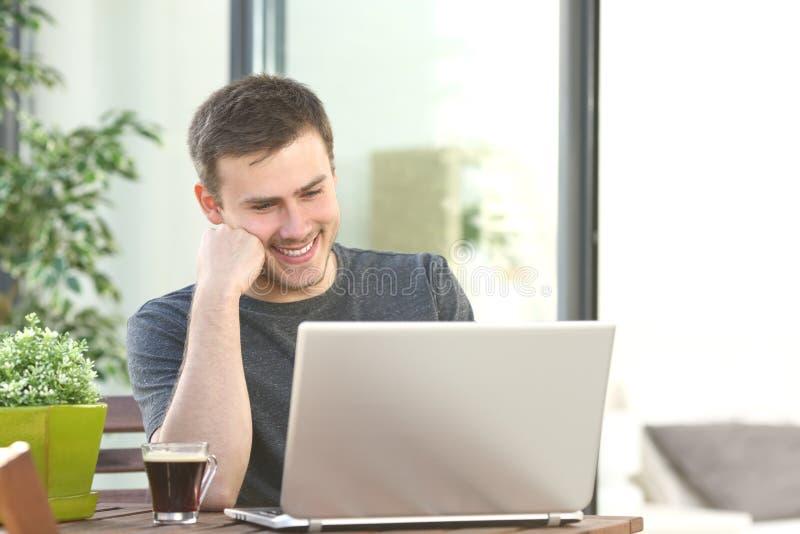 Sirva en línea con un ordenador portátil en un balcón imagenes de archivo