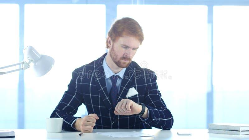 Sirva esperar en el trabajo, mirando tiempo en smartwatch imagen de archivo