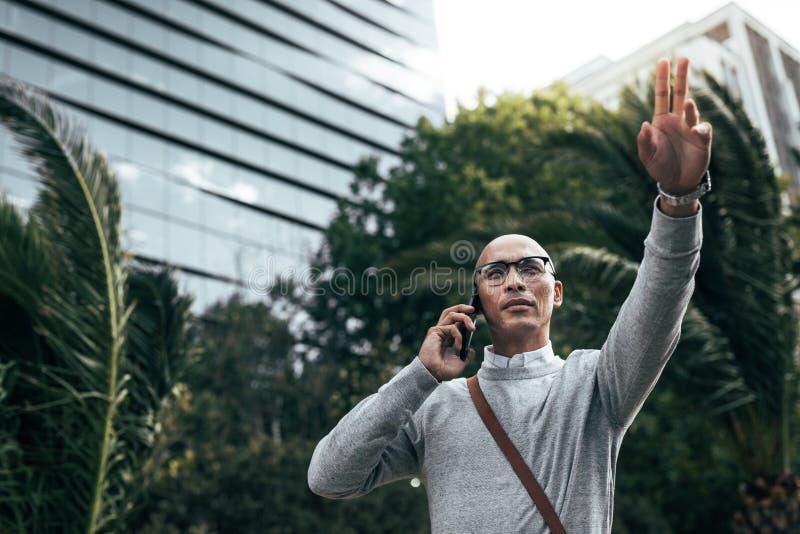 Sirva hablar en el teléfono móvil al aire libre que dice en voz alta con alguien foto de archivo