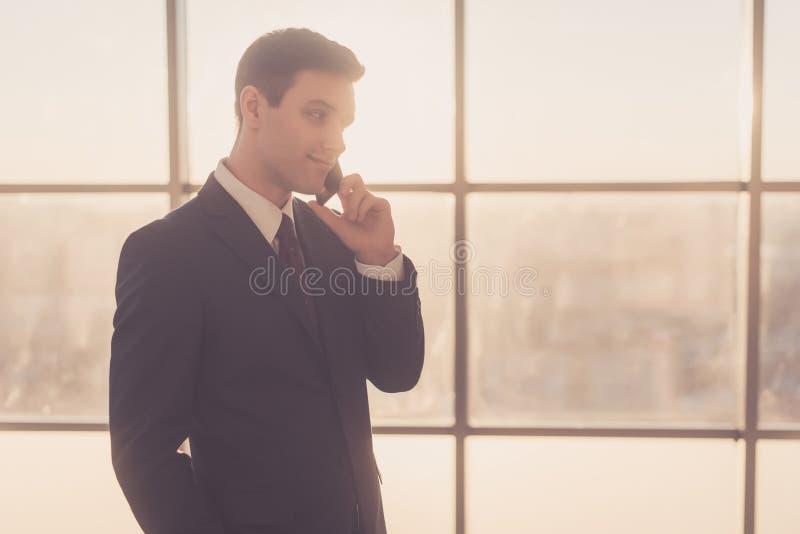 Sirva hablar en el teléfono mientras que se coloca en interior moderno con el espacio de la copia fotografía de archivo libre de regalías