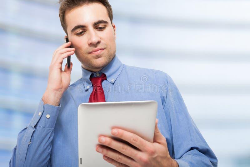 Sirva hablar en el teléfono mientras que usa su tableta fotos de archivo libres de regalías