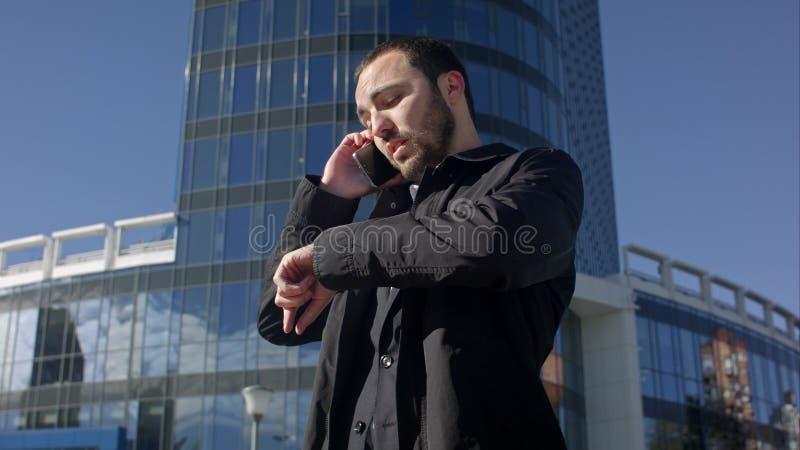 Sirva hablar en el teléfono y la mirada en su reloj al aire libre fotografía de archivo libre de regalías