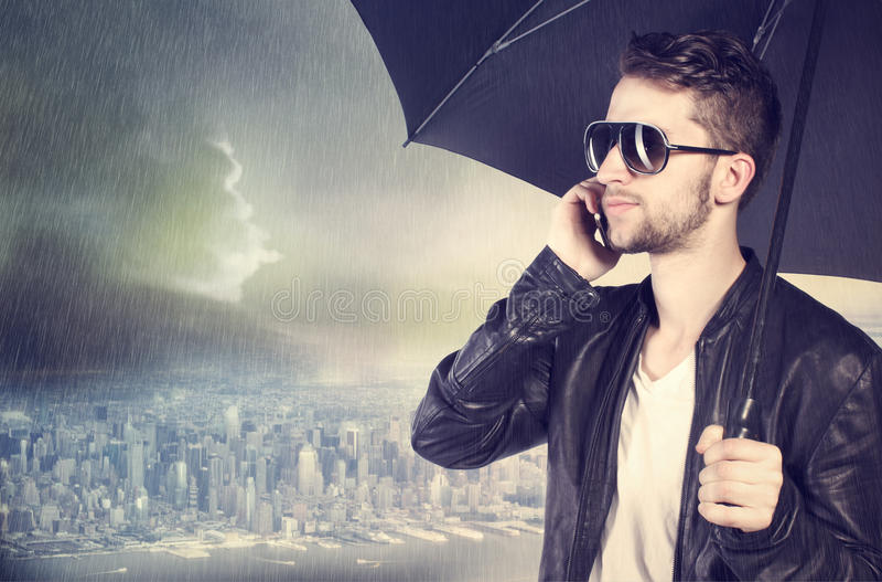 Sirva hablar en su teléfono celular en la lluvia foto de archivo