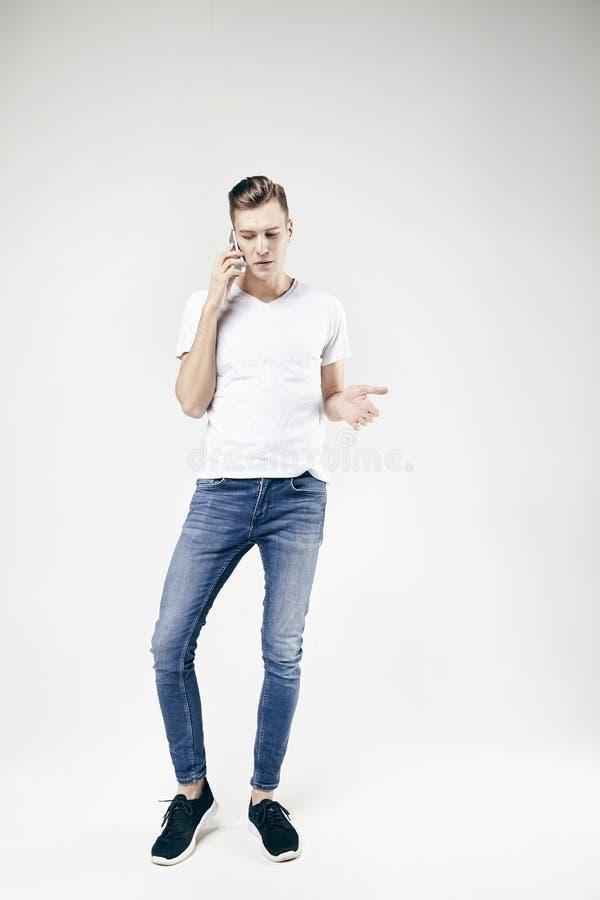 Sirva hablar modelo por vaqueros que llevan del teléfono móvil y la camiseta blanca, situación integral y demostración algo por l imagen de archivo