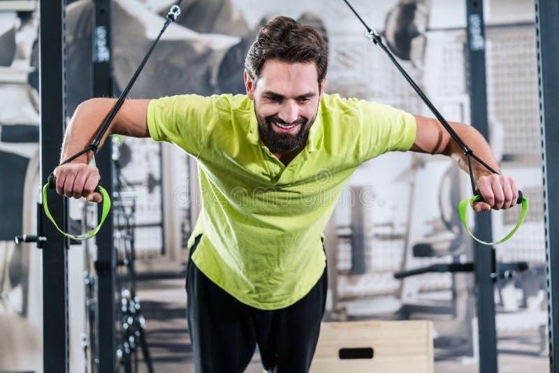 Sirva hacer flexión de brazos con los anillos en gimnasio funcional del entrenamiento fotos de archivo