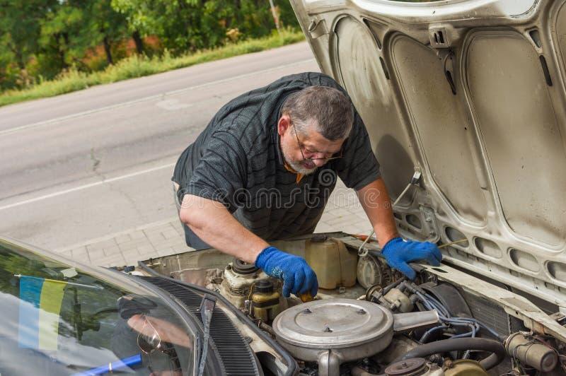 Sirva hacer poseen la reparación del coche en el camino foto de archivo