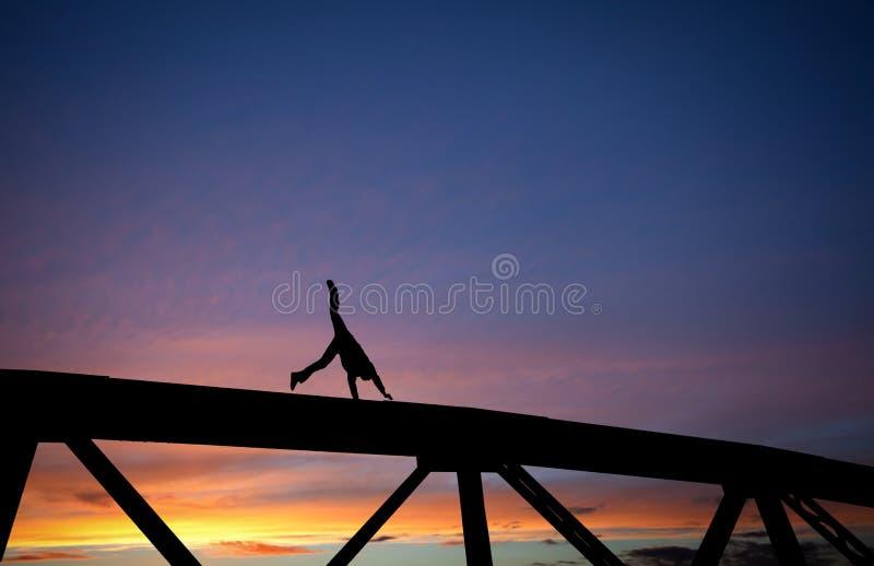 Sirva hacer un cartwheel en el puente de acero en la puesta del sol imagen de archivo libre de regalías