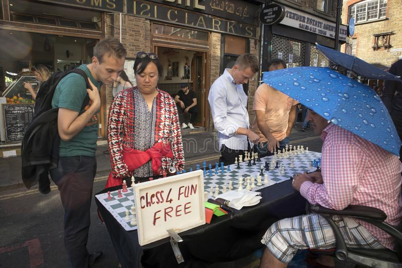 Sirva jugar a ajedrez con los transeúntes cerca en el carril del ladrillo, Londres La calle es el corazón de la comunidad del ban imágenes de archivo libres de regalías